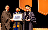 Associate Professor Patricia Isaac, center, was presented with the Chancellor's Award for Excellence by Executive Vice President Joseph Garcia and Associate Dean Nikki Shrimpton at the college's commencement ceremony at Syracuse.