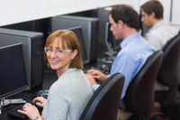 Woman seated in front of a computer in a lab, looks at the camera.