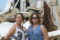 Associate Professor Audeliz Matias, left, and Associate Professor and Interim Director of European Academic Programs Sheila Marie Aird stand in front of a destroyed building in Puerto Rico.